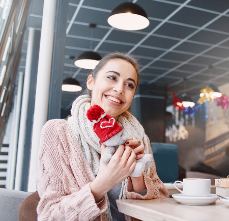 beguin: Two people, man and woman in cafe communicate, laughing and enjoying the time spending with each other. Couple in love on a date. A woman receives a gift from a man. Love story and Valentines Day concept