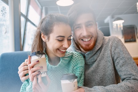 beguin: Man and woman drinking coffee in a cafe. Two people, man and woman in cafe communicate, laughing and enjoying the time spending with each other. Couple in love on a date. Love story and Valentines Day concept