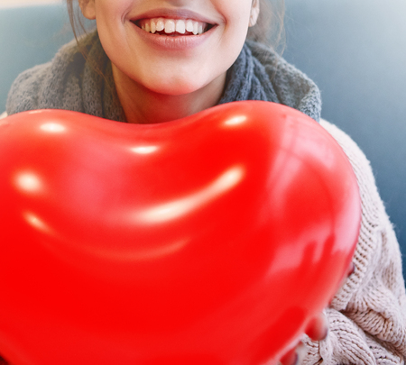 beguin: Happy smiling woman with balloon in the form of heart in a cafe. Couple in love on a date. Love story and Valentines Day concept