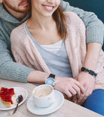 beguin: Two people, man and woman in cafe communicate, laughing and enjoying the time spending with each other. Couple in love on a date. Love story and Valentines Day concept. man embracing a woman sitting on the couch