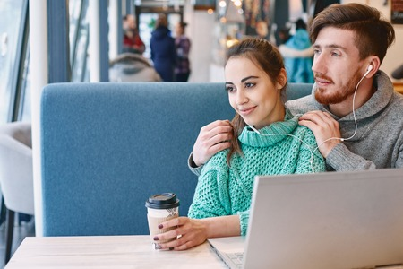 beguin: Man and woman drinking coffee and eating desert in a cafe. Two people, man and woman with laptop in cafe communicate, laughing and enjoying the time spending with each otherand. Couple in love on a date. Love story and Valentines Day concept Stock Photo