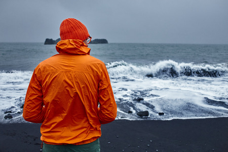 man walking along the beach in a storm. black sand beaches on the Atlantic coast in Iceland