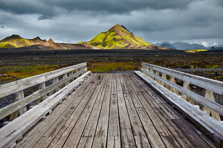 Wooden bridge over a river in ICELAND. Beautiful Icelandic landscape with mountains, sky and clouds. Trekking in national park Landmannalaugar Stock Photo