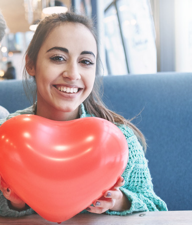 woman with balloon in the form of heart in a cafe. Couple in love on a date. Love story and Valentines Day concept