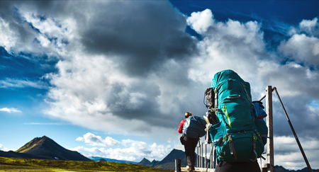 asher: two hikers on the trail in the Islandic mountains. Trek in National Park Landmannalaugar, Iceland. valley is covered with volcano asher