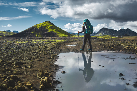asher: woman hiker on the trail in the Islandic mountains. Trek in National Park Landmannalaugar, Iceland. valley is covered with volcano asher