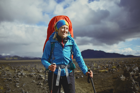 asher: woman hiker on the trail in the Islandic mountains. Trek in National Park Landmannalaugar, Iceland. valley is covered with volcano asher. Dramatic cloudy sky Stock Photo