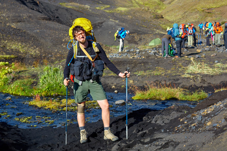 asher: man hiker on the trail in the Islandic mountains. Trek in National Park Landmannalaugar, Iceland. valley is covered with volcano asher.