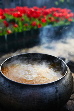 Cast-iron cauldron with soup at the stake in the courtyard. Summer day and dinner in the fresh air near the flower bed. Homemade bricks with cast iron lid