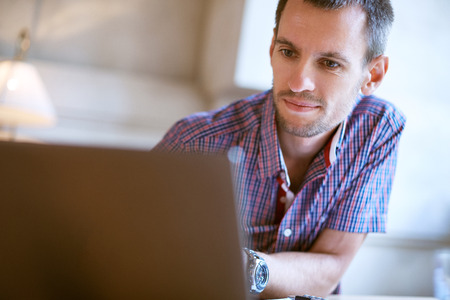 Man sitting at the table in the office and looks at laptop. On the desk is a laptop and papers, documents. Concept of business or education Stock Photo