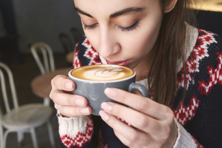 prety: young woman at cafe drinking coffee and smiling. woman sits alone at the wooden table. Woman dressed in a knitted sweater, face and palms with cup close up