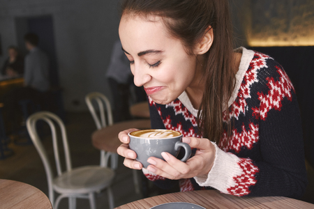 prety: young woman at cafe drinking coffee and smiling. woman sits alone at the wooden table. Woman dressed in a knitted sweater