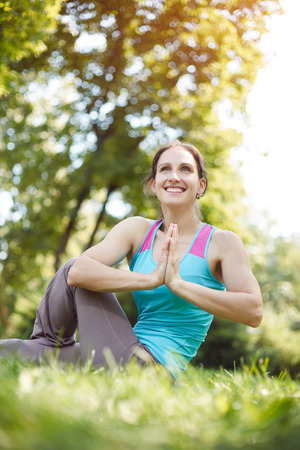 teaches: Yoga outdoor. Happy woman doing yoga exercises, meditate in the park. Yoga meditation in nature. Pretty athletic girl practices and teaches yoga in the park. Concept of healthy lifestyle and relaxation.