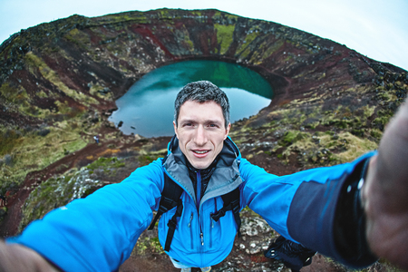A man shoots a selfie in the background of a volcano crater. A trip through the golden ring of Iceland in the middle of autumn Stock Photo