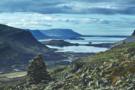 Beautiful view of the Iceland fjord. A trip to Iceland in the fall. Stones and a trail in the foreground, in the background the sea, mountains and sky