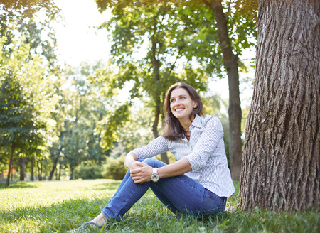 Cute young woman looking like a student sitting in a park on the grass under a tree. On her big headphones, near her is a book Stock Photo