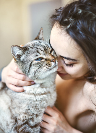 Happy beautiful young woman in the morning in bed with a cat. A woman without clothes and covered with a blanket. Morning photograph with a natural light from the window at home. Good mood and a pleasant start to the day Stock Photo