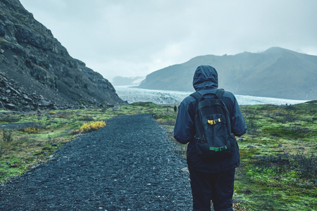 tourist going to Glacial lagoon in Iceland in the fall. Cloudy foggy weather, mountains on the horizon.