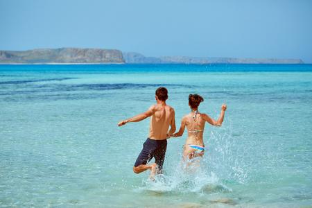 jong gelukkig paar dat op het strand loopt. Balos-strand, Kreta, Griekenland.
