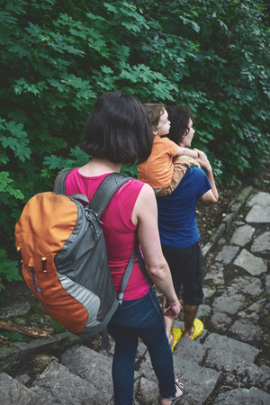 Family with child Hiking In Countryside Wearing Backpacks