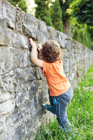 A little boy tries to climb a stone wall at summer evening in city park.