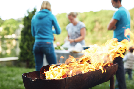 outdoor fireplace: flame grilled and wood burning in fire. family BBQ party in outdoor or home garden. people on background is out of focus.
