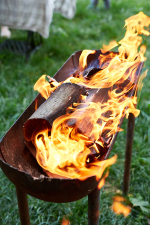 flame grilled and wood burning in fire. family BBQ party in outdoor or home garden. fireplace on the grass. Stock Photo