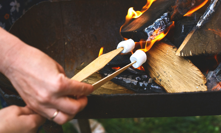 outdoor fireplace: flame grilled and wood burning in fire and hands with Sticks with marshmallows on fire close up. family BBQ party in outdoor or home garden.