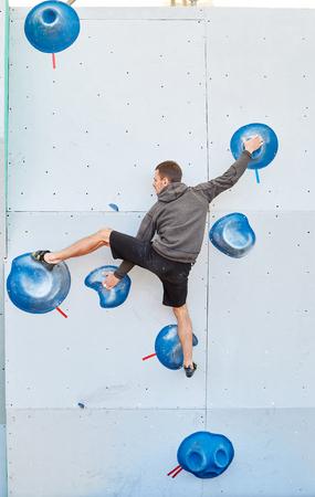 man climber climbs a bouldering problem on climbing gym. man mekes hard wide move. Climbing competition Stock Photo - 80000375