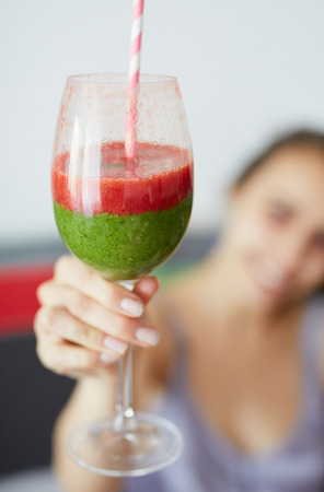 smiling woman with glass of strawberry smoothies with a green spinach cocktail. focus on the glass, woman is blured