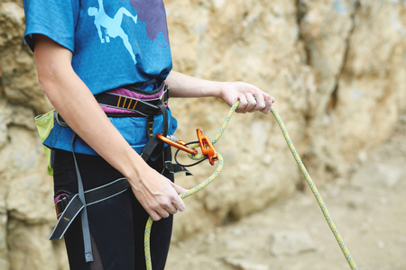 woman belaying other climber through a belay device. Tubular device on locking carabiner. hands and belay device close up Stock Photo