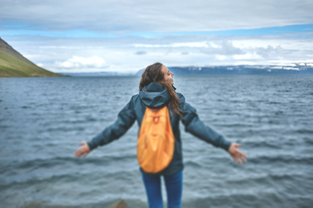 part of me: Young girl outstretching hand asking to follow her on background of sea, Iceland, West Fjords. blured image