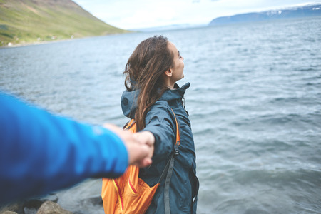 part of me: Young laughing girl outstretching hand asking to follow her on background of sea, Iceland, West Fjords. Foto de archivo