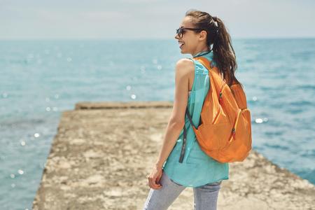 part of me: La muchacha de risa joven con la pequeña mochila anaranjada se coloca en el embarcadero en el fondo del mar