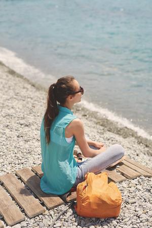 part of me: La muchacha de risa joven con la pequeña mochila anaranjada se sienta en la cobertura de madera en la playa en el fondo del mar Foto de archivo