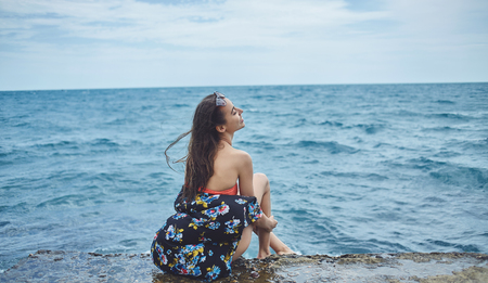 part of me: Young laughing girl wearing in bikini sits on background of sea
