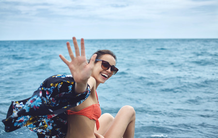 part of me: Young laughing girl wering in bikini outstretching hand asking to follow her on background of sea Foto de archivo