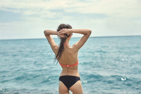 part of me: Young cheerful girl wearing in bikini stands on pier on background of sea. back view