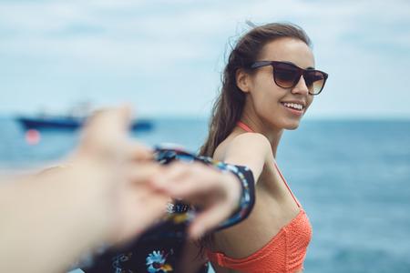 part of me: Chica joven riendo wering en bikini extendiendo la mano pidiendo seguirla en el fondo del mar. céntrese en la mujer