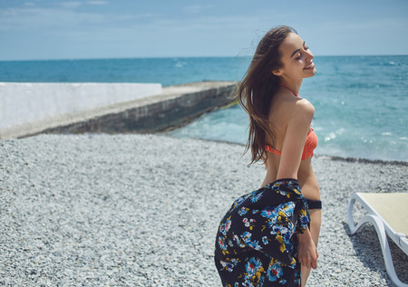 part of me: Young cheerful smiling girl wearing in bikini stands on pier on background of sea. back view