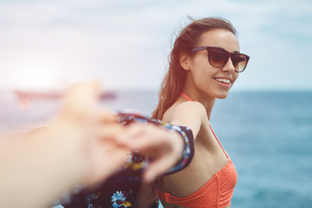 part of me: Young laughing girl wering in bikini outstretching hand asking to follow her on background of sea. focus on the woman