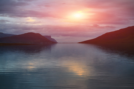 Travel to Iceland. beautiful sunset over the ocean and fjord in Iceland. Icelandic landscape with mountains, sky and clouds. Stock Photo