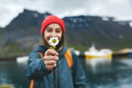 Back view of girl in warm clothing with backpack on pier with background of mountains of West Fjords, Iceland. woman hold the flower in hand and give it to the camera, focus on flower Stock Photo