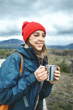 Girl in warm clothing and red hat hold a iron cup and drink a hot tea on background of mountains of Iceland.