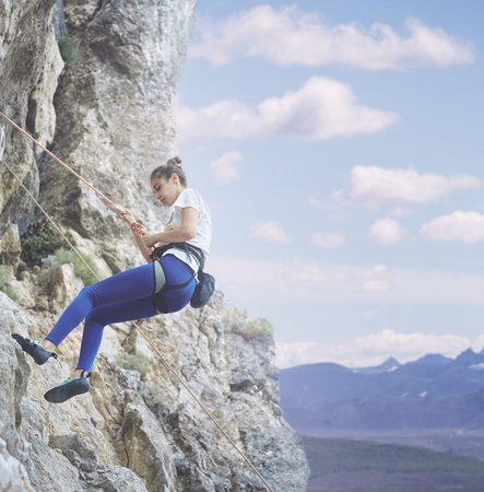 young cheerful woman climbs on the cliff. rock climber Learns to climb rocks on a rocky wall. woman makes hard move and looking up Reklamní fotografie