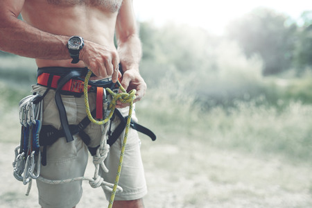 A man climber Knots a knot on a climbing harness. hands in chalk close up