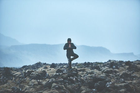Woman in waterproof clothing stands in yoga pose on volcanic Lava fields on background of mountains of Iceland. Stock Photo