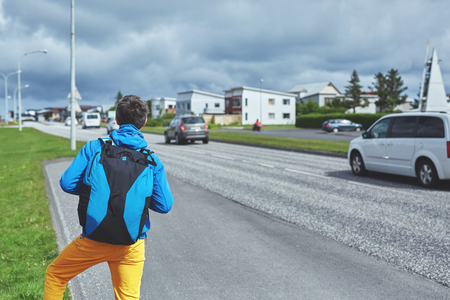 voyage: man traveler with backpack stops the car on the road
