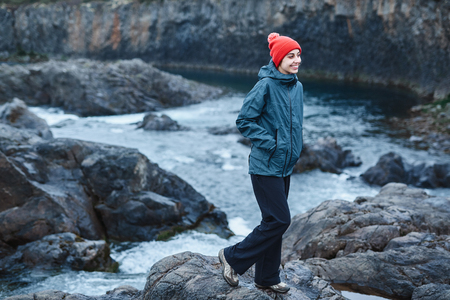 north cascade national park: a woman tourist in waterproof clothes and red hat stands on the Bank of the mountain river with small waterfall. Glanni waterfall, Iceland Stock Photo