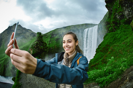 smiling woman in warm clothes making selfie on a Skogafoss waterfall background, Iceland. Focus on the woman